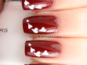 Rimmel Rapid Ruby with white stencilled hearts nails